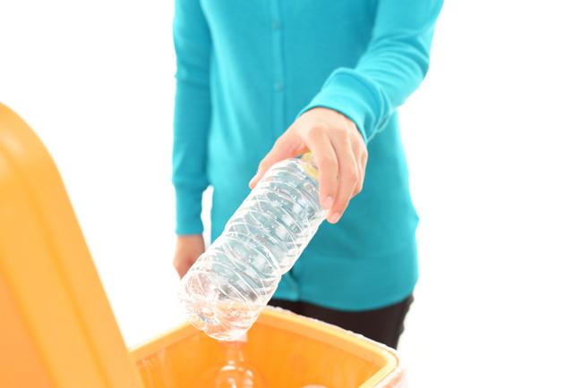 ペットボトルをゴミ箱に捨てる女性