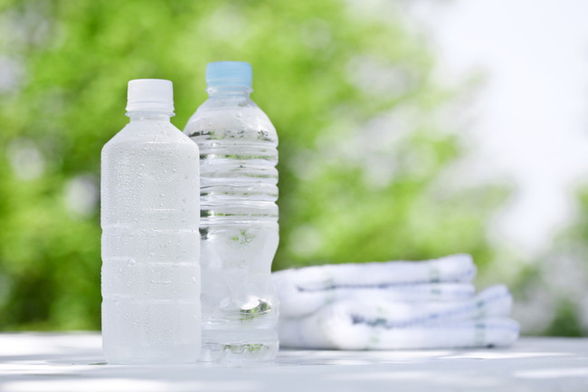 木の前にある2本のペットボトルの水とタオル