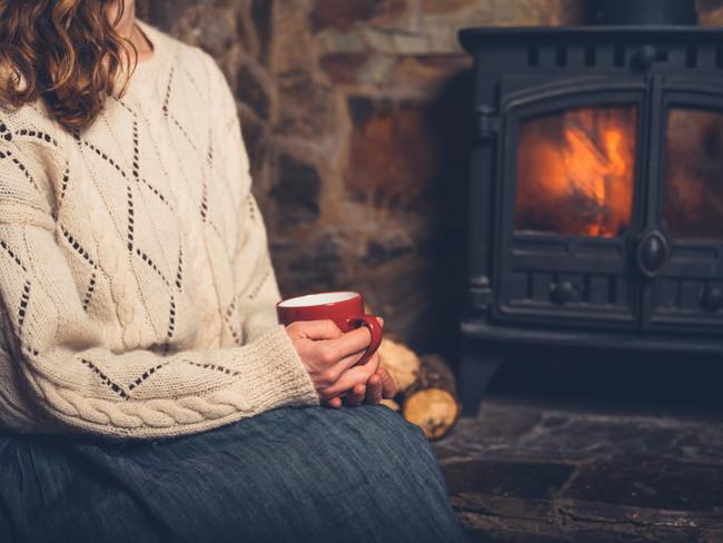 暖炉の近くで暖を取っている女性