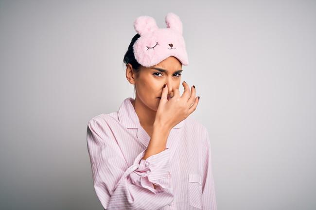 パジャマを着て鼻をつまんでいる女性