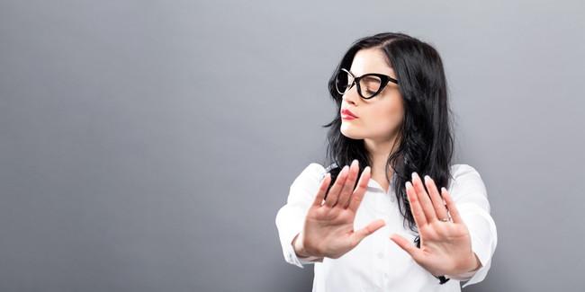 両手をつき出しNOを表わしている女性