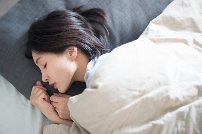 ベッドで横向きになって熟睡している女性