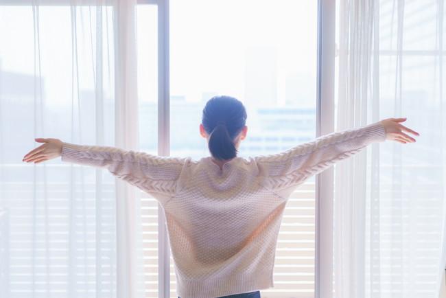 窓を開け外の空気を吸いながら深呼吸している女性