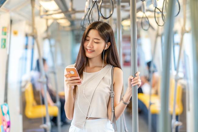 電車の中でイヤホンを使いスマホの音楽を聴いている女性