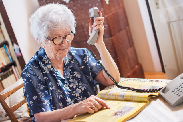 電話帳を見て電話する老人