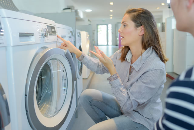 洗濯機のスイッチを押す女性