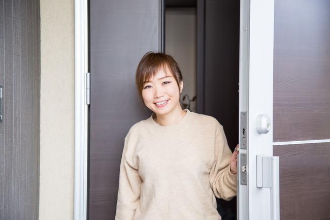笑顔で玄関から出てくる女性