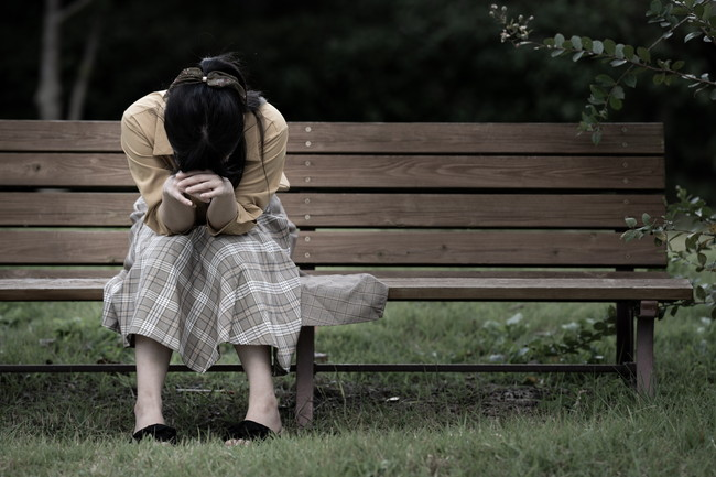 ベンチに座って落ち込む女性