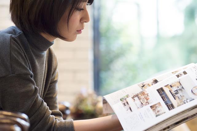 雑誌のスクラップ読む女性
