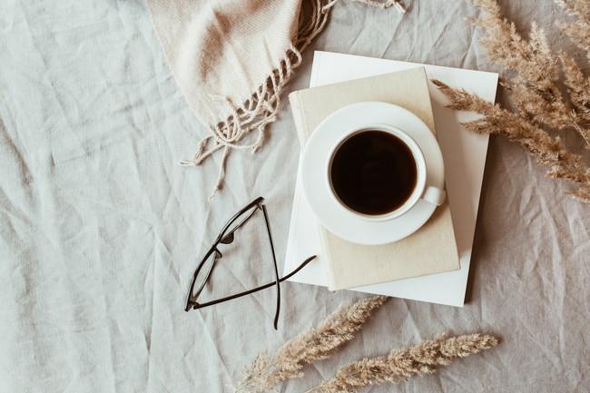 白い布の上のコーヒーとメガネ