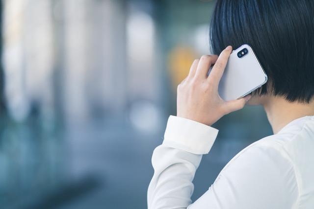 電話をかける白いシャツの女性