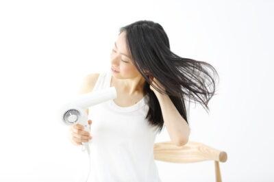 ドライヤーで髪を乾かすロングヘアの女性