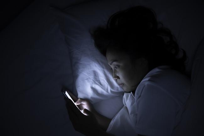 寝る前にベッドの中でスマホを見ている女性