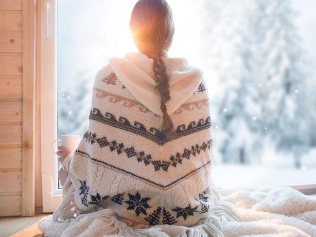 コーヒーカップを持ちながら外の雪景色を見ている女性の後ろ姿