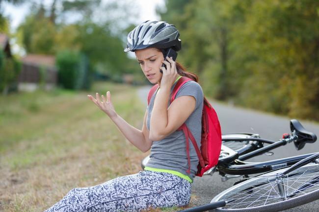 倒れた自転車と困った様子で電話をしている女性