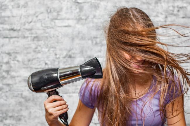 髪にドライヤーの風を当てている女性