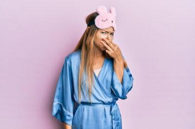 臭そうに鼻をつまんでいるパジャマを着た女性