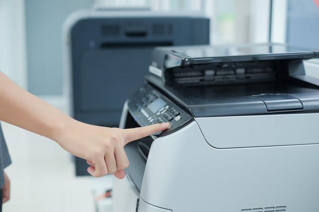 コピー機のボタンを人差し指で押す