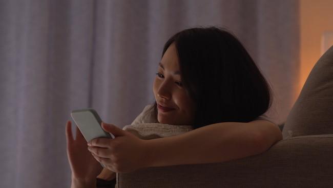 夜更かしをしながらスマホを見ている女性