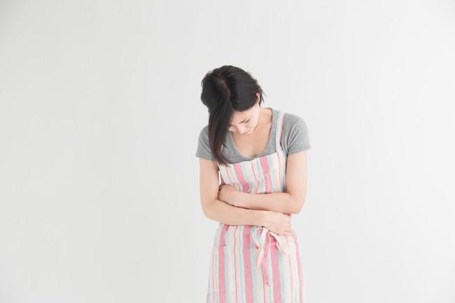 腹部を抑えてうつむいているエプロン姿の女性