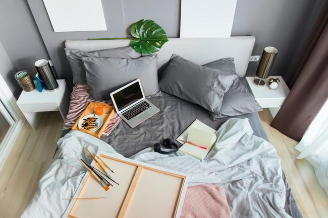 仕事道具が置かれごちゃごちゃしているベッド