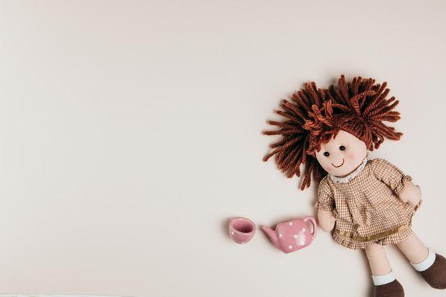 白い背景の上の人形とおもちゃのお茶セット