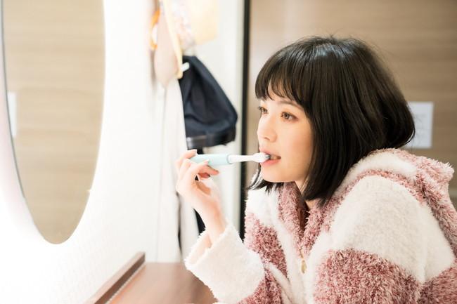 電動歯ブラシで歯を磨く女性