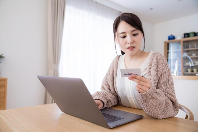 カードを見ながらパソコンを操作する女性