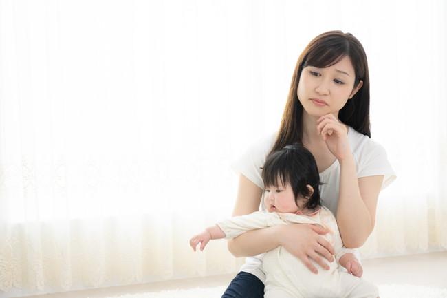 赤ちゃんを抱いて浮かない顔をしている女性