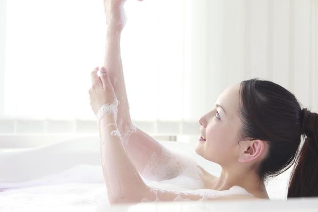 泡のお風呂で身体を洗う女性
