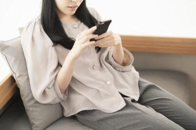 ソファでくつろぎながらスマホを操作している女性