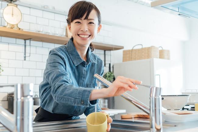 キッチンで食器洗いしている女性