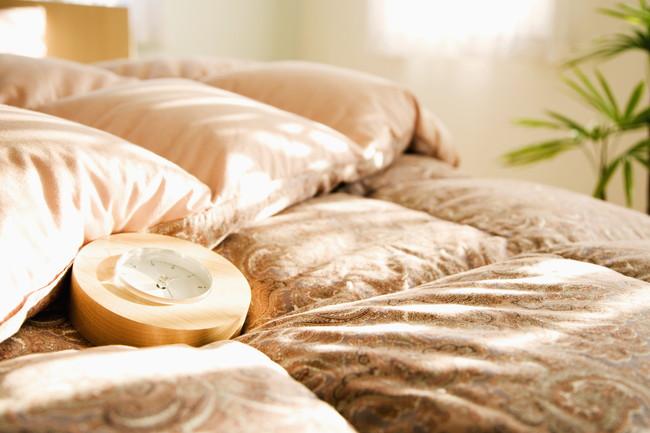 朝の日差しとベッドの上の羽毛布団