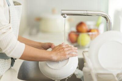 キッチンで食器洗いをしている女性
