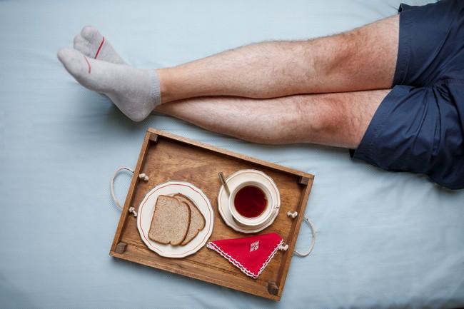 寝具の上でお茶をしている男性