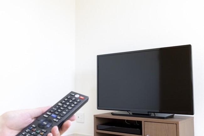 リモコンでテレビを操作している