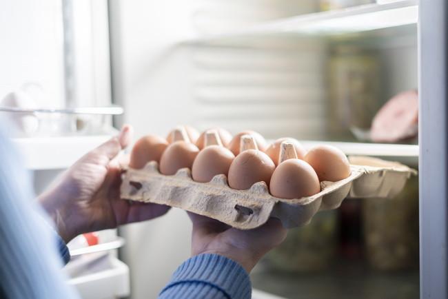 冷蔵庫にパック入り卵を入れるところ