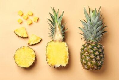 丸ごと、様々にカットされたパイナップル、オレンジ系の背景