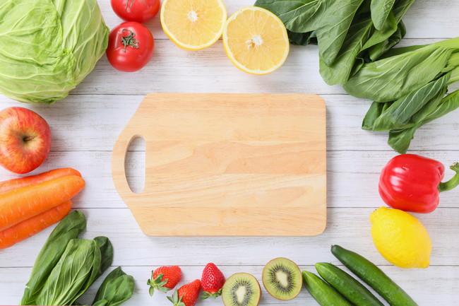 緑黄色野菜に囲まれた木製のまな板