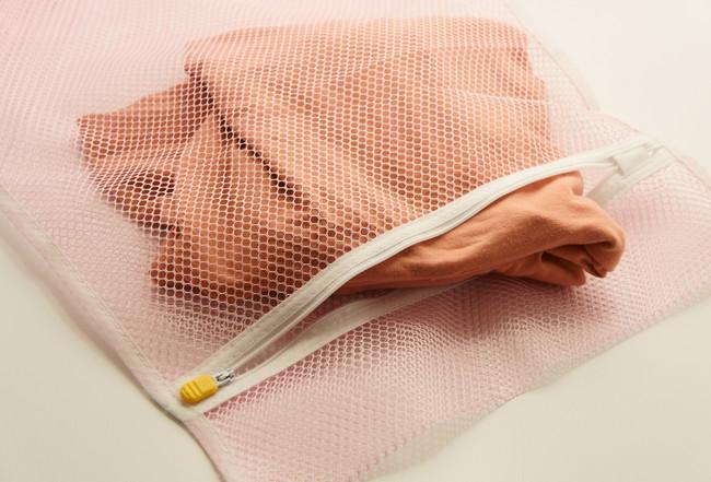 洗濯ネットとピンクのセーター
