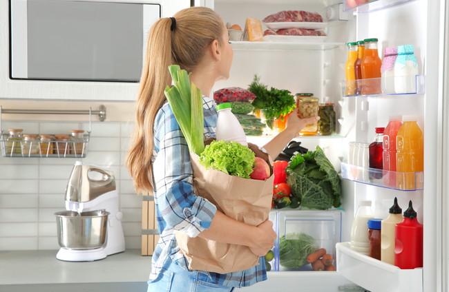 冷蔵庫へ食材を入れている女性