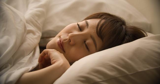 羽毛布団をかけて熟睡している女性