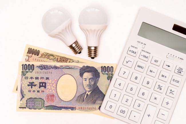 電卓とお札と電球で電気代のイメージ