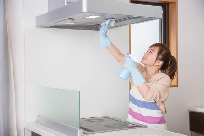 ゴム手袋を着けて換気扇を掃除する女性