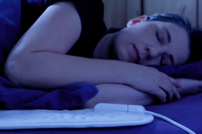 電気毛布を使って眠っている女性