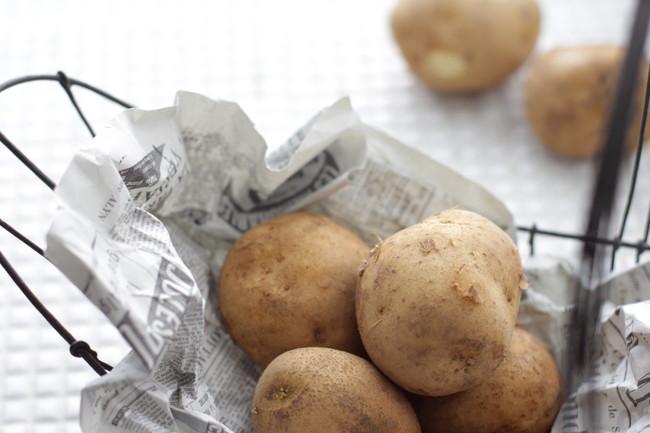白いタイルの上で新聞紙に包まれて保存してるジャガイモ