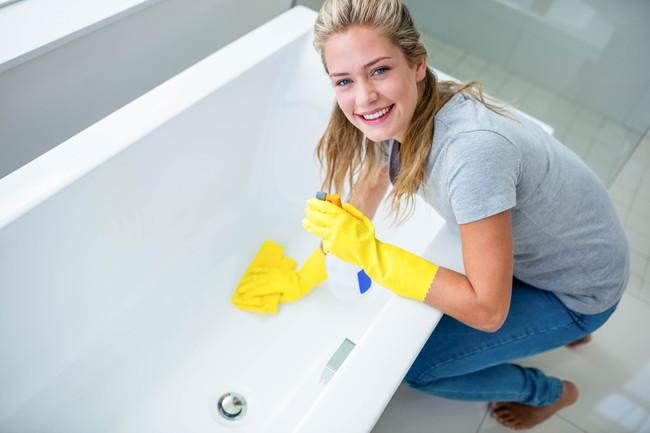 ゴム手袋を着けて浴槽を掃除している女性