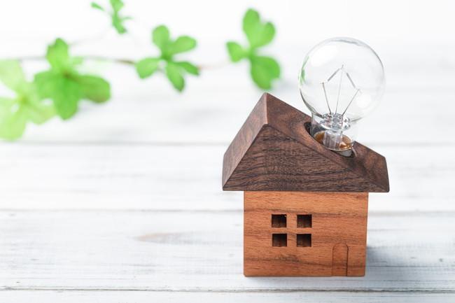 ミニチュアハウスと電球で電気代のイメージ