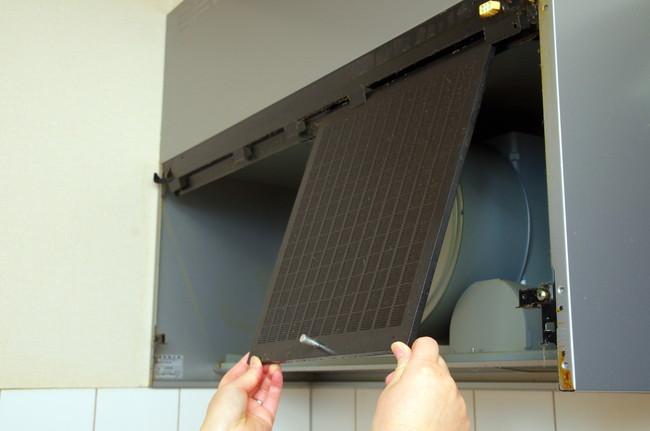 キッチン換気扇のレンジカバーを取り付けているところ