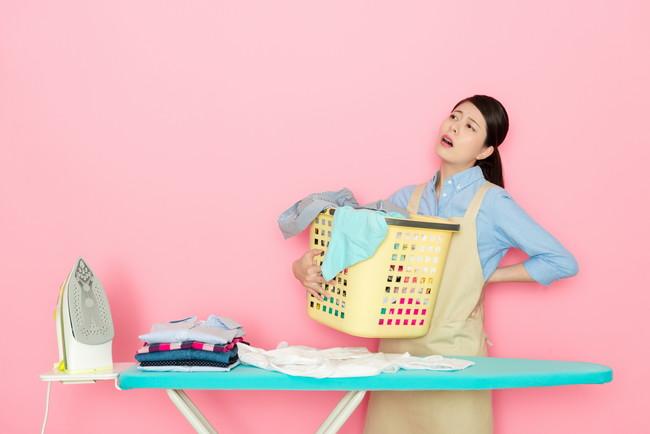洗濯カゴを抱えて疲れた様子でアイロン台の前に立っている女性
